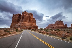 The Organ massive sandstone rock tower seen along Arches Scenic Drive with dramatic storm clouds looming overhead, Arches National Park, Moab, Utah