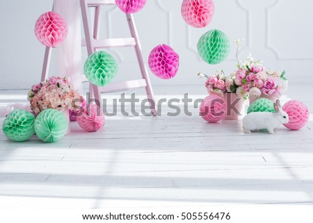 The original bright decor for birthday girl.Pink and green decorative paper balls. White Room decorated with flowers and paper decorations for party.Small white rabbit
