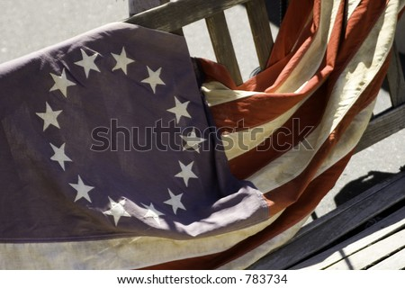 The original 13 colonies American flag laying on a wooden bench.