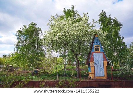 The original colorful wooden garden toilet in the village, on the site against the backdrop of tall tall green leafy trees. Garden exterior. Russian outdoor toilet.  #1411355222