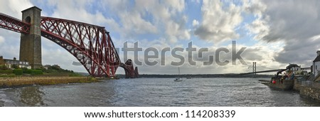 The original Forth Rail Bridge and the newer Forth Road Bridge stretch side by side from the harbor at North Queensferry across the waters of the Firth of Forth towards Edinburgh.