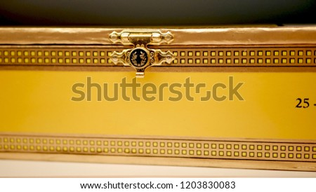 The ornate latch of a wooden cigar box, yellow and gold designs along the edge. #1203830083
