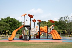 The outdoor playground in the daytime has a backdrop of green trees and blue skies.