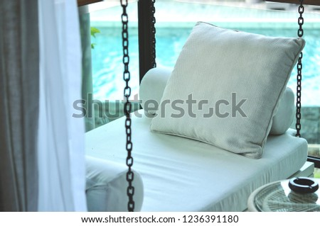 The outdoor porch swing sitting is located at the corner of the terrace outside room with swimming pool background, this area for reading, relaxing or drinking tea. #1236391180