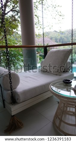 The outdoor porch swing sitting is located at the corner of the terrace outside room with swimming pool background, this area for reading, relaxing or drinking tea. #1236391183