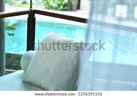 The outdoor porch swing sitting is located at the corner of the terrace outside room with swimming pool background, this area for reading, relaxing or drinking tea. #1236391192