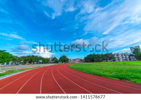 The outdoor track and field track is under the blue sky and white clouds.