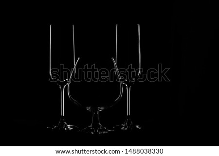 The outlines of transparent glass goblets on a black background. #1488038330