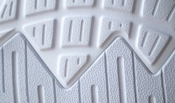 The outsole of new white sneakers. Rubber sole for men's shoes. Sole for sports and walking shoes. The texture of the material of sports shoes.