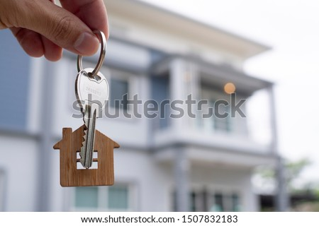 The owner holds a new home key from a real estate dealer. House for sale and for rent concept.