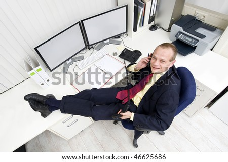 The owner of a small business relaxing behind his desk making several phone calls