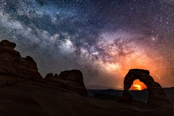 The Pack Creek Fire in the La Sal Mountains lights up the night sky in the distance, with the Milky Way over Delicate Arch in Arches National Park, Utah.