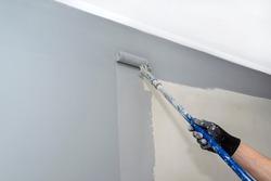 The painter paints the room gray with a paint roller on an extended stick at home.