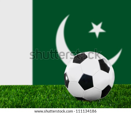 The Pakistani flag and soccer ball on the green grass
