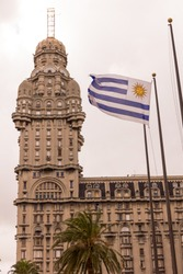 The Palacio Salvo and the Uruguayan flag, in the independence square of Montevido, the center of the capital of Uruguay, two emblems or icons of the country and the city. Montevideo, Uruguay
