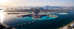 The Palm island panorama with Dubai marina rising in the background aerial view