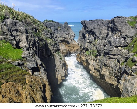 The pancake rocks and blow holes of Punakaiki on the South Island of New Zealand.  These ancient formations are the most visited natural attraction on the West Coast of the island.