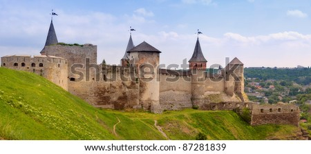 The panorama of old fortress with ramparts and towers. The high stone walls. In the foreground is green hill, below of the fortress on the background - the city. Sunny day. Ukraine.