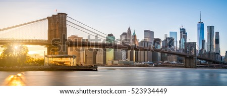 The panorama view of Brooklyn Bridge with Lower Manhattan in the background, lit by sunset #523934449