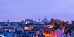 The panorama view of famous Taj Mahal and Agra town, India at the morning dawn with pink cloudy sky