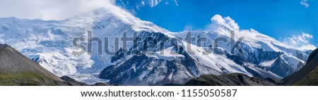 The panoramic mountain view with rocks and ice in Tian Shan mountains in Central Asia near Almaty covered by clouds. Best place for active life, climbing, hiking and trekking in Kazakhstan. #1155050587