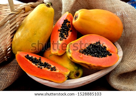The papaya fruits in a wooden pot and a straw basket and rustic fabric at the background