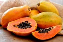 The papaya fruits on a wooden table and a rustic fabric at the background