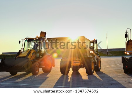 The parade of trucks. Road construction machines in the rays of the setting sun.  #1347574592