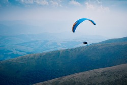 The paraglider is flying in the sky above mountains. Image toning.