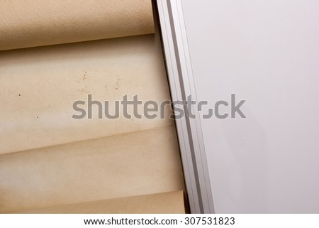 The parchment is rolled into a scroll, next to the board of plastic.