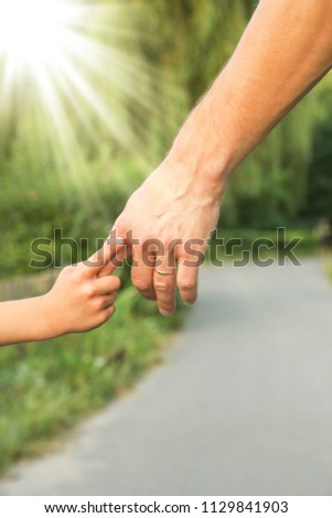the parent holding the child's hand with a happy background #1129841903