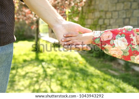 the parent holds the hand of a small child #1043943292