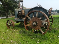 The park of old tractor. The old tractor on the garden. The old tractor on the blue sky background. Rusty of old tractor