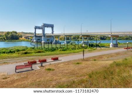 The park on the riverbank and bridge above river. Don river, Russia, Rostov-on-Don region, stanitsa Kazanskaya. #1173182470