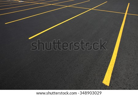 The parking stalls in a parking lot, marked with yellow lines. #348903029