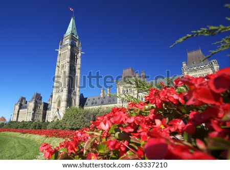The Parliament of Canada with red flowers in the foreground