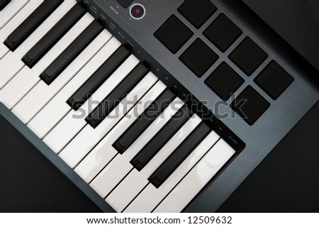 The Part of Professional MIDI-keyboard with 8 trigger pads on black background - stock photo