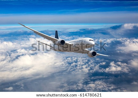 The passenger plane in flight. Aircraft flies high in the blue sky over clouds. Front view.