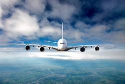 The passenger plane in flight. Aircraft flies high in the blue sky through the clouds. Airplane front view.