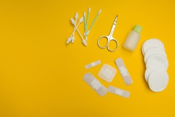 The patches of different sizes and shapes and wool for treatment of wounds on a yellow background