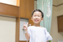 The patient kid is happy in the hospital, He has a cheerful heart.