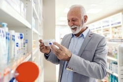 The patient reads the statements on the packaging of the drug at the pharmacy. A senior man with a smile in an elegant suit holds a package of medical drugs and reads the statement and expiration date