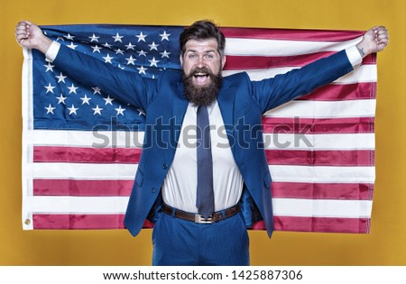 The patriotic spirit. Patriotic man holding american flag on independence day. Bearded businessman being patriotic for usa. The average american is nothing if not patriotic. #1425887306