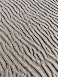 The pattern left by the sea on sand. The sun creating light and shadow in the ripples.