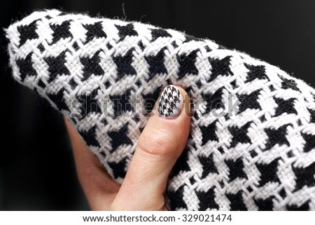 The pattern on the nails, black and white manicure. Woman\'s hand with fingernails painted in black and white checkered