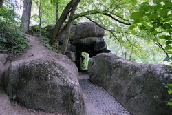 The paved path through a tunnel under the huge stones overgrown with trees and bushes. Dendrological park Sofiyivka, Uman Ukraine.