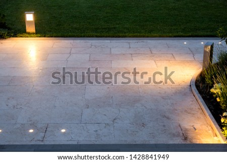 The pavement of marble tiles and a stone border area in the evening illuminated by ground lanterns in a metal housing shining a warm light around the lawn. #1428841949