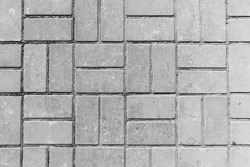 The pavement path is laid out of rectangular tiles.