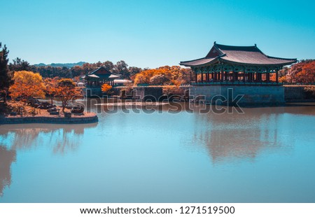 Photo of  The pavilions of Anapji Pond reflected in the water in Gyeongju.The Gyeongju Historic Areas of South Korea were designated as a World Heritage Site by UNESCO in 2000, ref 976. Teal and orange view.