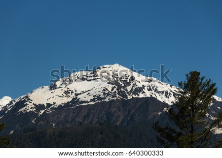The peak mountain cover with snow and light blue sky at  Shogarn area northern Pakistan in summer season #640300333